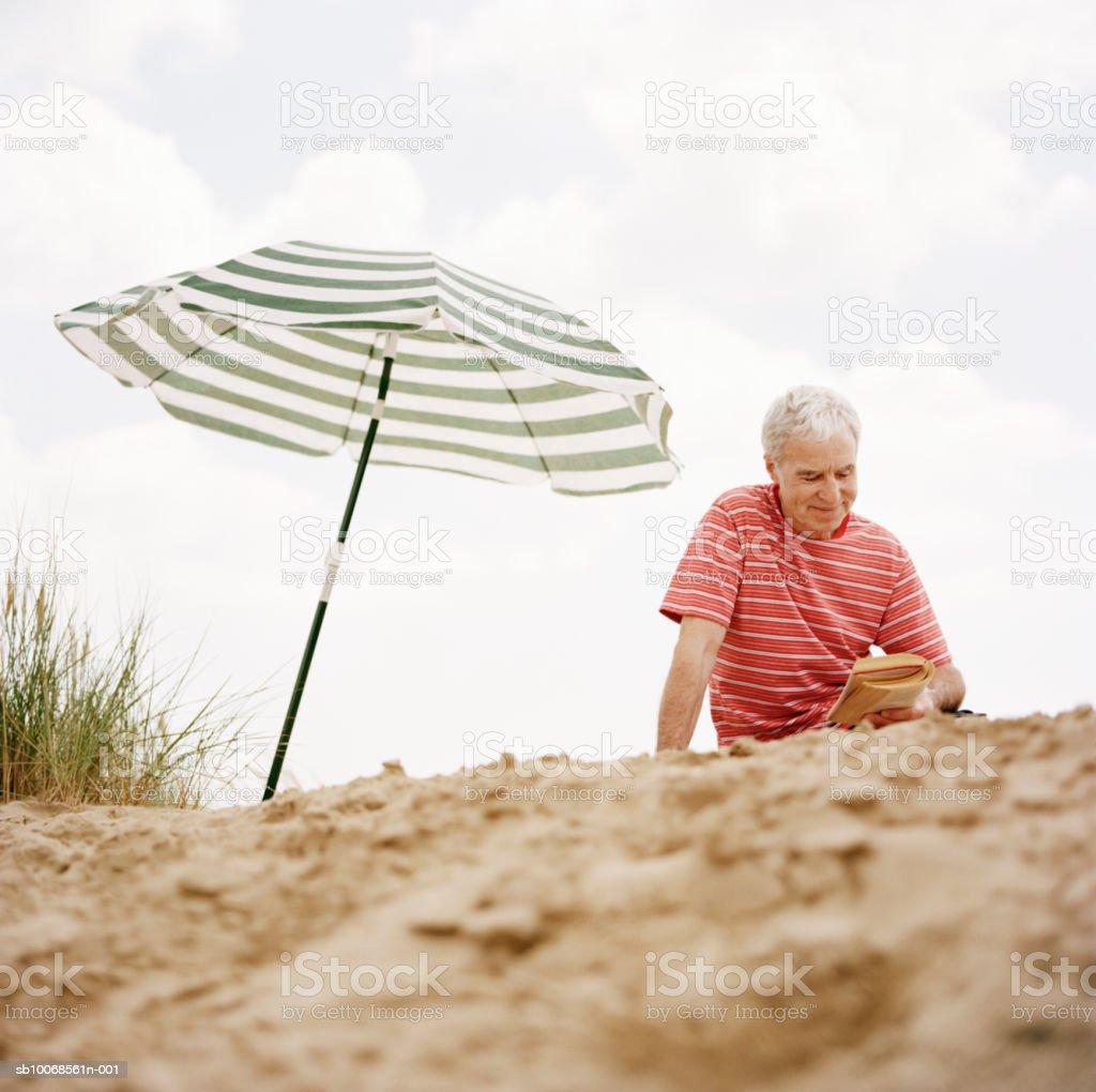United Kingdom, Rye, Camber Sands, man reading beside umbrella on beach royalty-free stock photo