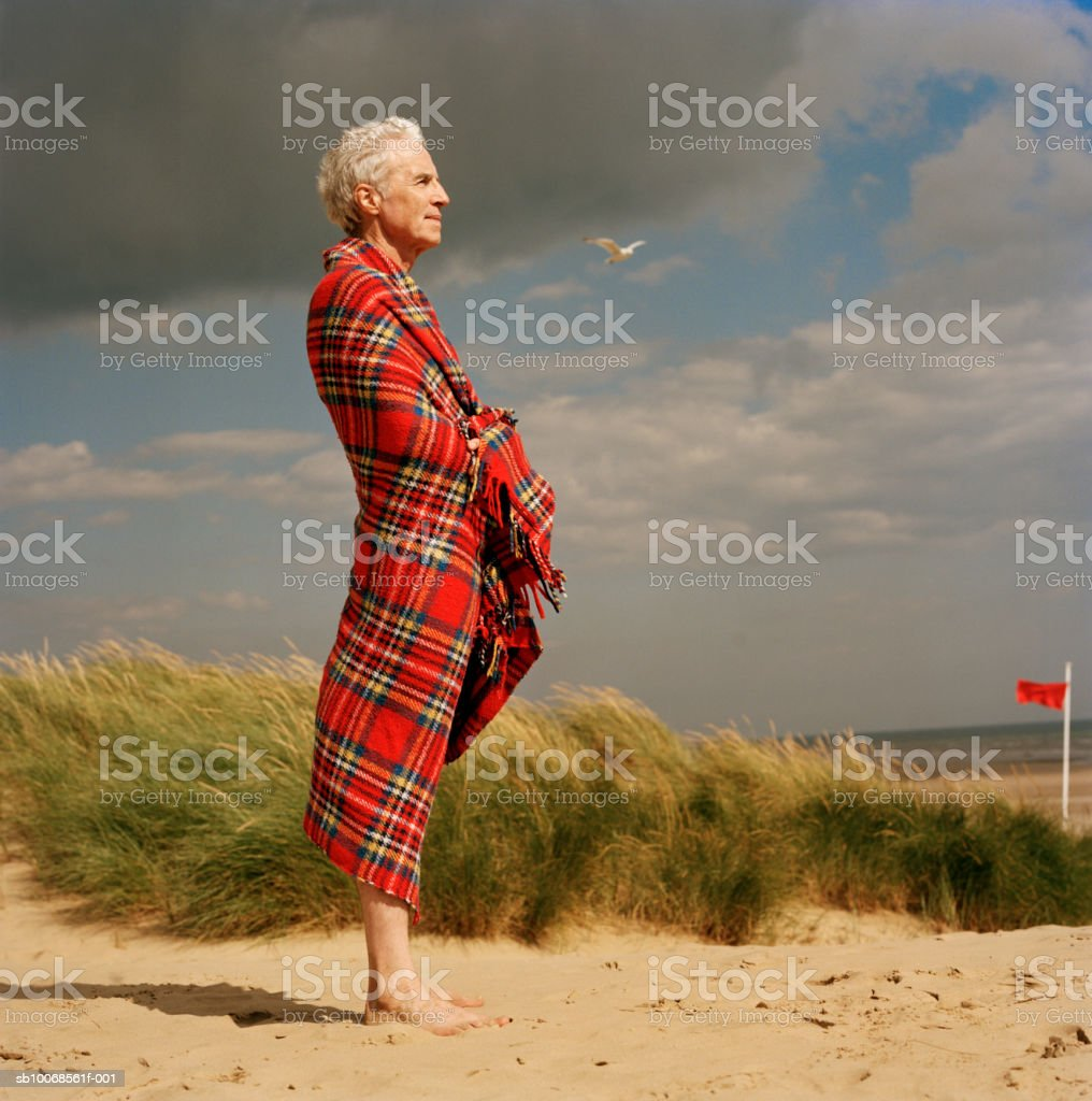United Kingdom, Rye, Camber Sands, man wrapped in blanket at beach royalty-free stock photo