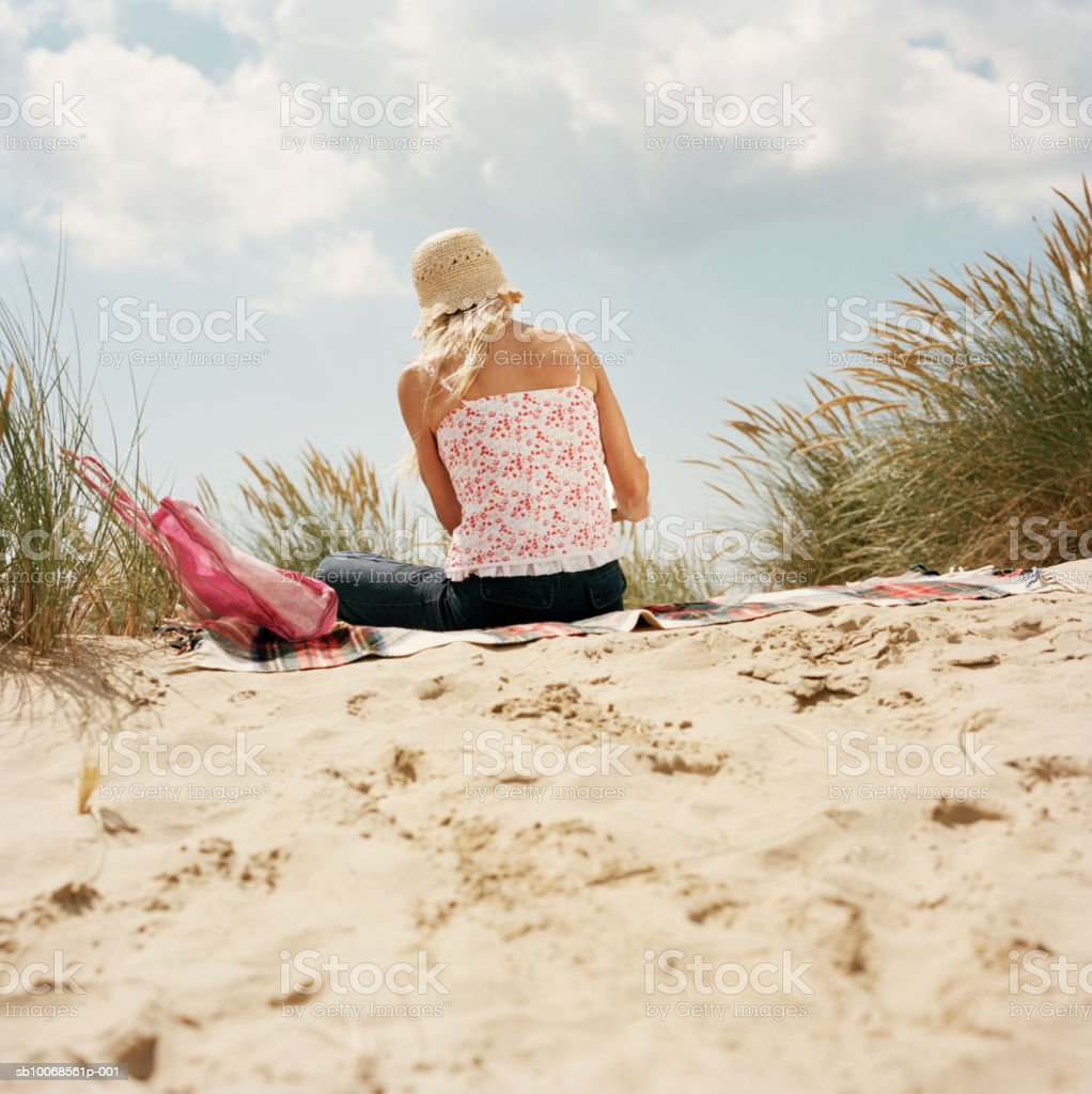 United Kingdom, Rye, Camber Sands, woman reading on sand dunes royalty-free 스톡 사진