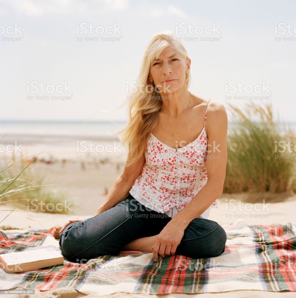 United Kingdom, Rye, Camber Sands, woman sitting on blanket at beach, portrait foto de stock libre de derechos