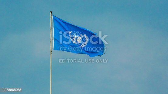 Geneva, Switzerland - Aug 16, 2020: flag with Emblem of United Nations building isolated against blue sky. European headquarters of UN.