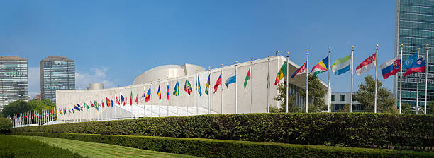 un united nations general assembly building with world flags - united nations стоковые фото и изображения