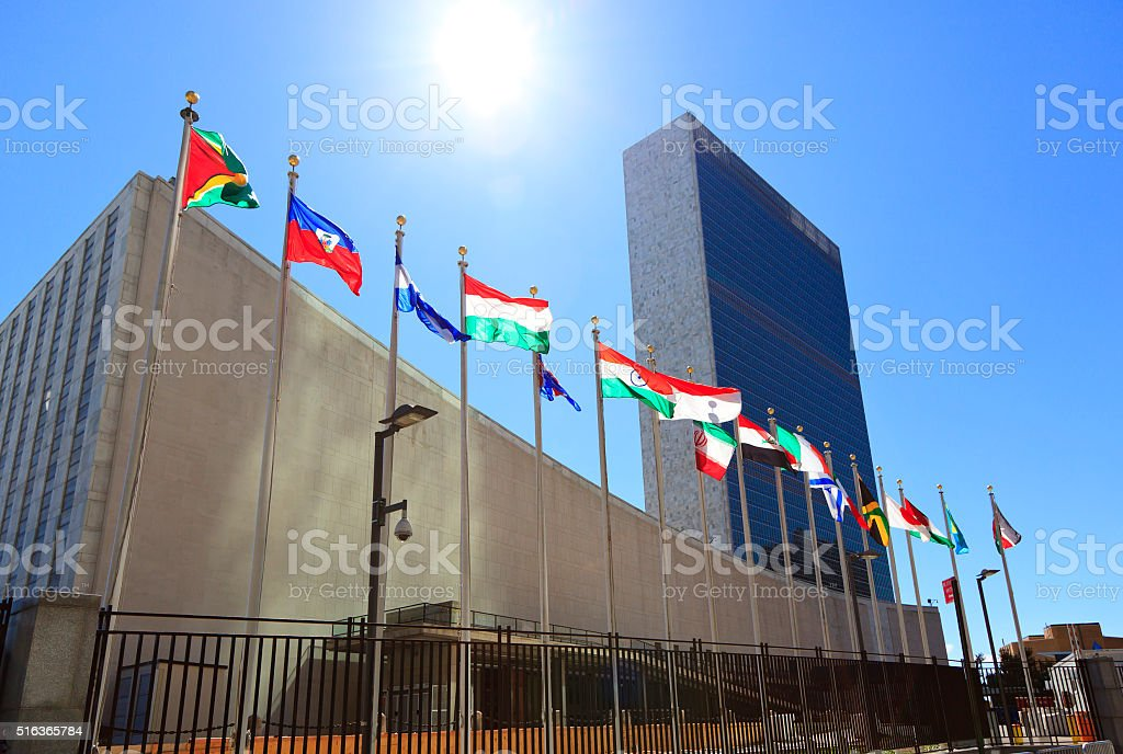 United Nations Headquarters with waving flags in New York, USA stock photo