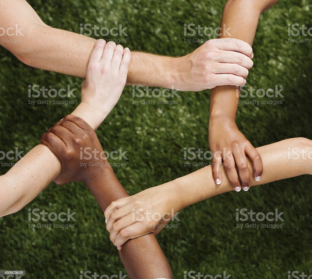 United Nations of hands: five hands clasped against grassy background stock photo
