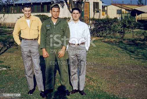 Three US Air Force Soldiers pose in front of military barracks in Chinae South Korea.  The soldiers were on leave from the war and were staying at the Naval base.