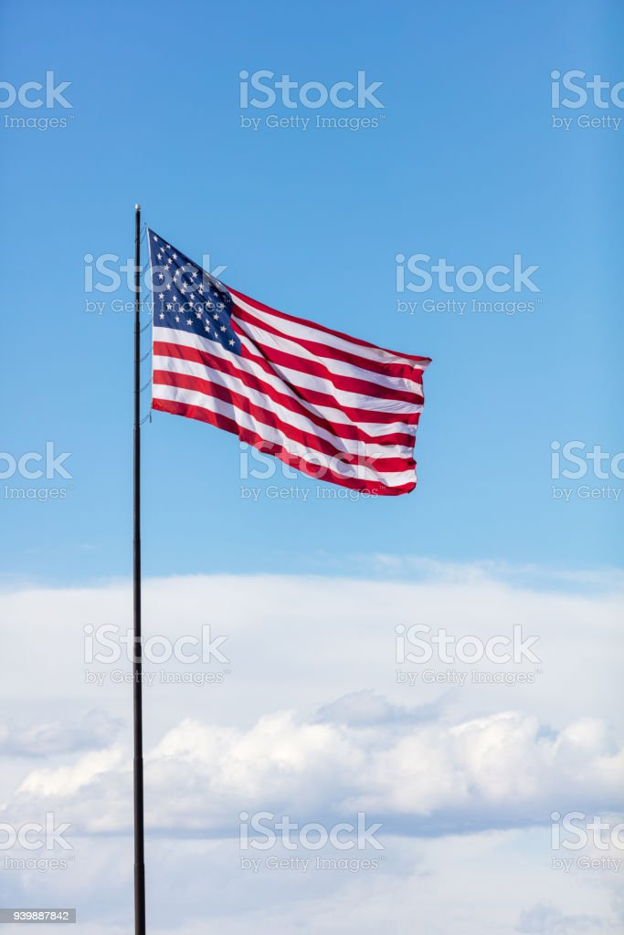 United States American Flag on a sunny windy day with a cloudscape background stock photo
