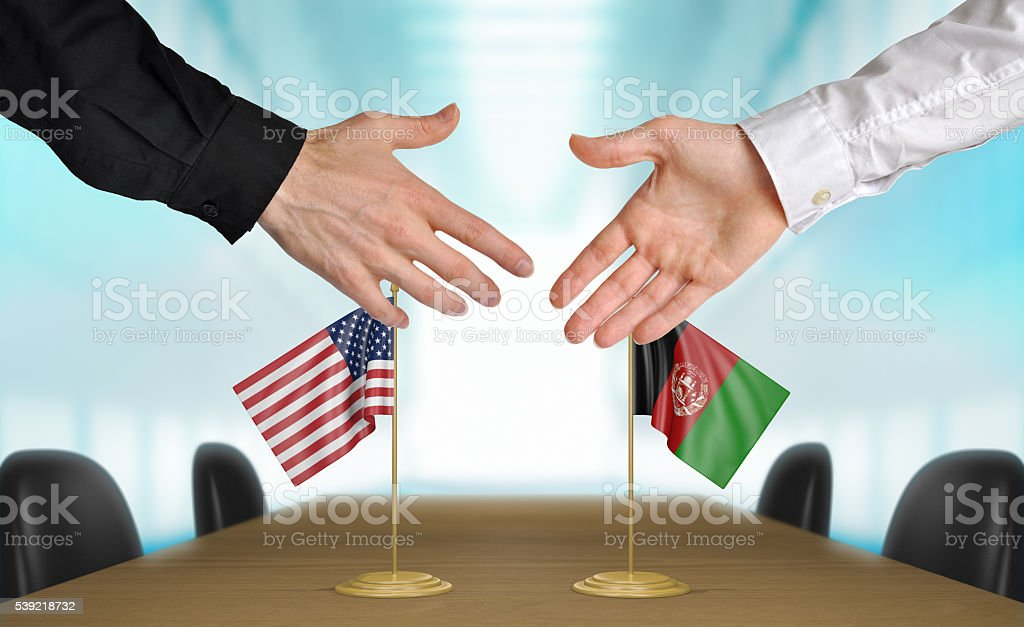 United States and Afghanistan diplomats shaking hands to agree deal stock photo