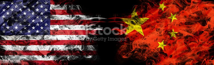 American and Chinese flags in smoke shape on black background. Concept of conflict war and custom duty. America VS China metaphor. Dollar Yuan exchange currency and international commercial tension.