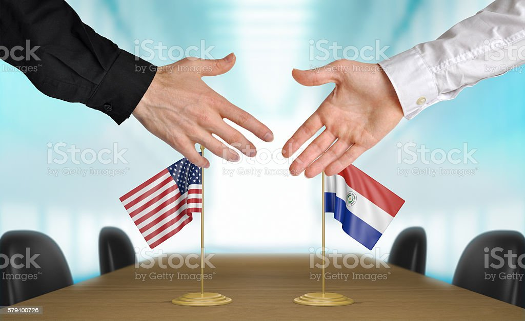 United States and Paraguay diplomats shaking hands to agree deal stock photo