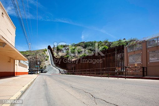 United States border wall with Nogales Mexico behind on the right