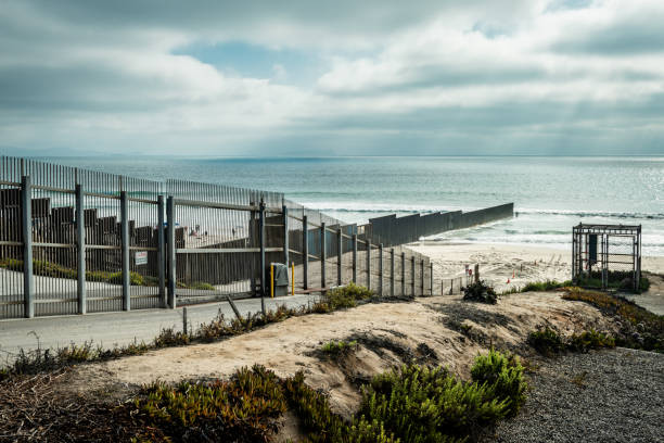 United States Border Wall with Mexico at the Pacific Ocean in California View from the California side of the US/Mexico border into Tijuana where the border fence meets the Pacific Ocean international border barrier stock pictures, royalty-free photos & images