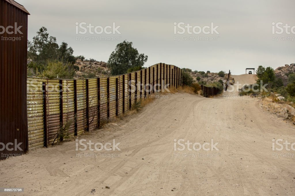 United States Border Wall with Mexico Jacumba, CA - NOVEMBER 27: United States international wall with Mexico and Border Patrol vehicle in the distance on November 27, 2017 in Jacumba, CA, USA. Baja California Peninsula Stock Photo