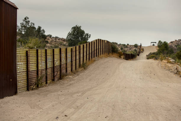 United States Border Wall with Mexico Jacumba, CA - NOVEMBER 27: United States international wall with Mexico and Border Patrol vehicle in the distance on November 27, 2017 in Jacumba, CA, USA. international border barrier stock pictures, royalty-free photos & images
