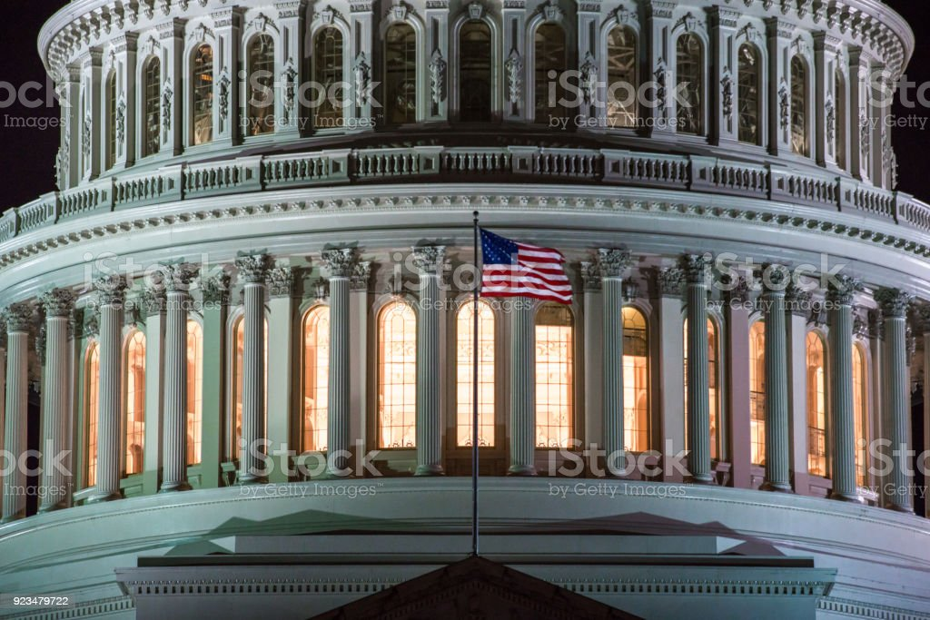 United States Capitol Dome Close Up and American Flag at Night in Washington, DC stock photo