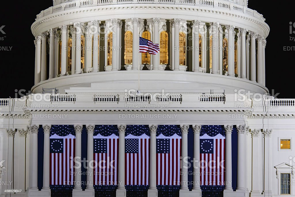 United States Capitol with American flags draped between columns stock photo