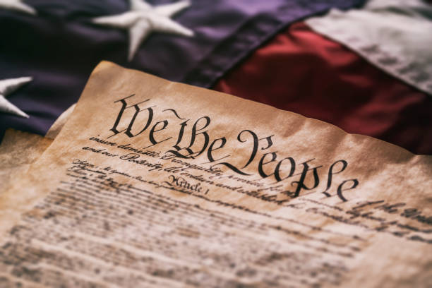 United States Constitution on American Flag We The People - An old USA Constitution on parchment paper lying on a old American flag. distressed american flag stock pictures, royalty-free photos & images