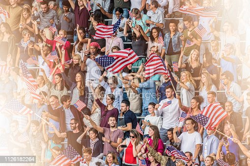 Large group of people standing on stadium bleachers waving American flags during a sports event.