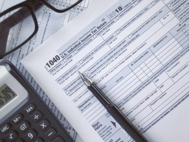 United States federal income tax concept. United States federal income tax return IRS 1040 documents, with pen calculator and eyeglasses. income tax stock pictures, royalty-free photos & images