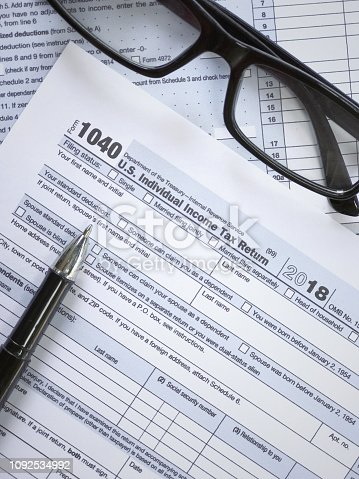 United States federal income tax return IRS 1040 documents, with pen and eyeglasses.