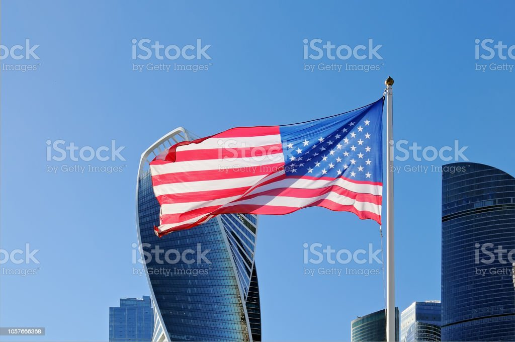 Usa flag fluttering on flagpole against the background of Moscow City...