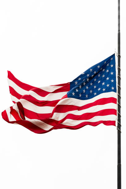 United States Flag Flying at a Half-staff Waving Against Gray Sky stock photo