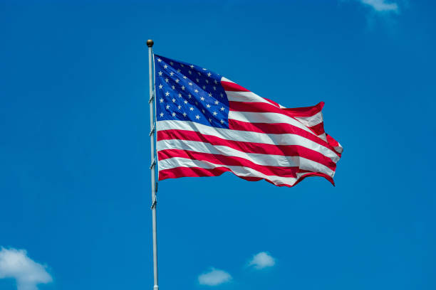 United States flag flying in blue sky with few clouds stock photo