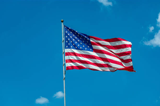 United States flag in blue sky stock photo