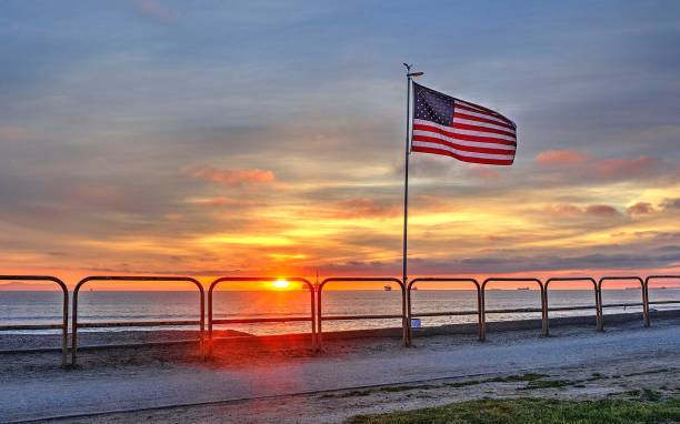 United States Flag over the Pacific Ocean as the sun sets stock photo