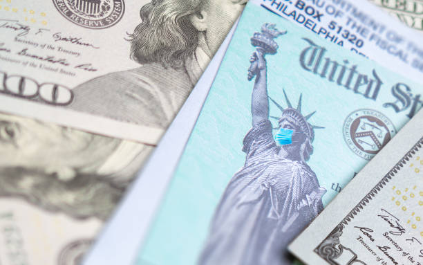 United States IRS Stimulus Check with Statue of Liberty Wearing Medical Face Mask Resting on Money United States IRS Stimulus Check with Statue of Liberty Wearing Medical Face Mask Resting on Money. stimulus check stock pictures, royalty-free photos & images
