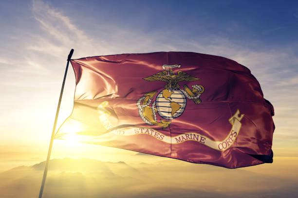 United States Marine Corps flag textile cloth fabric waving on the top sunrise mist fog stock photo