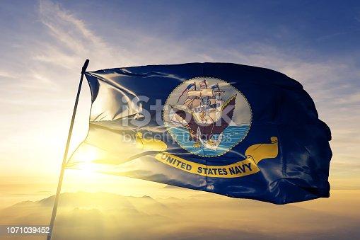 United States Navy flag on flagpole textile cloth fabric waving on the top sunrise mist fog