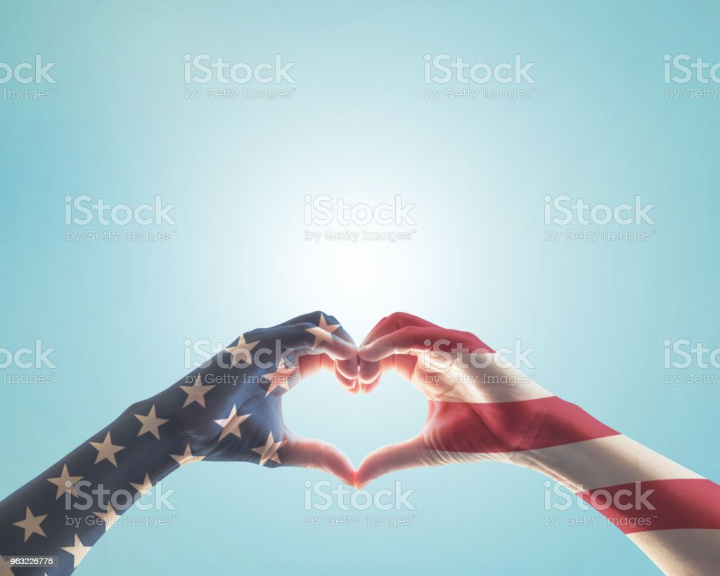 United States of America -USA American flag pattern on people hands in heart love shape isolated on blue sky background stock photo