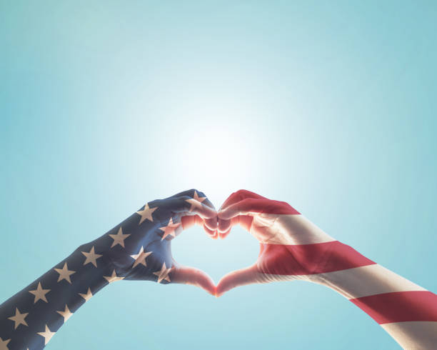 États-Unis d'Amérique-USA American motif drapeau sur le peuple des mains en forme d'amour de coeur isolé sur fond de ciel bleu - Photo