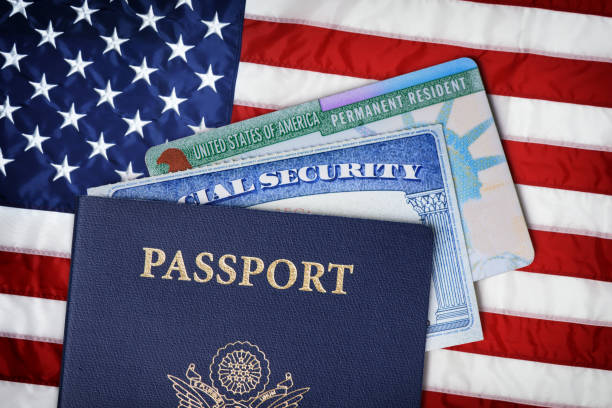 United States passport, social security card and resident card over American flag. Immigration concept stock photo