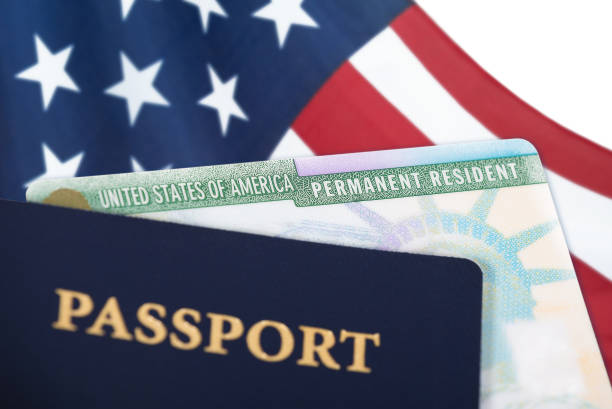 United States resident card, immigration concept United States of America permanent resident card, green card, displayed with a US flag in the background and a passport in the foreground. Immigration concept. department of homeland security stock pictures, royalty-free photos & images