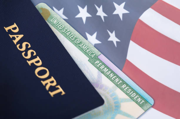United States resident card, immigration concept United States of America permanent resident card, green card, displayed with a US flag in the background and a passport in the foreground. Immigration concept. green card stock pictures, royalty-free photos & images