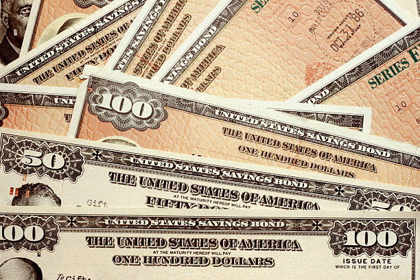 united states savings bonds of varying amounts - stock certificate stock photos and pictures