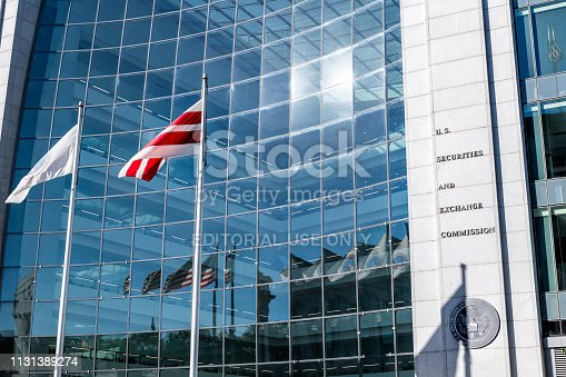 Washington DC, USA - October 12, 2018: United States Securities and Exchange Commission SEC architecture closeup with modern building sign and logo with red flags by glass windows