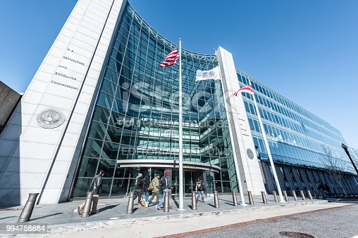 istock US United States Securities and Exchange Commission SEC entrance, people walking, sign, entrance, american flag, looking up sky, glass windows reflection 994758684
