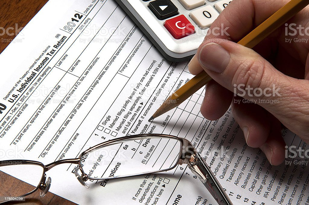 United States tax form with hand sharpened pencil calculator glasses royalty-free stock photo