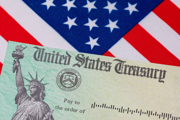 United States Treasury check and American flag. Concept of stimulus payment, tax refund. Federal government grants, loans, benefits and assistance stock photo