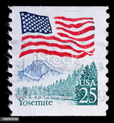 UNITED STATES OF AMERICA - CIRCA 1988: A used postage stamp printed in United States shows a waving USA flag above the Yosemite National Park California, circa 1988