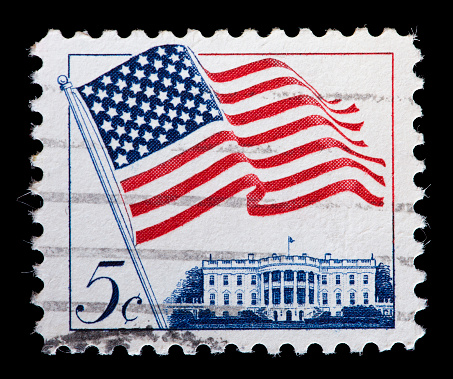UNITED STATES OF AMERICA - CIRCA 1963: A used postage stamp printed in United States shows a USA flag waving against Government buildings, circa 1963