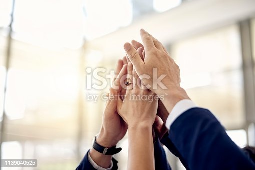 Closeup shot of a group of businesspeople giving each other a high five in an office