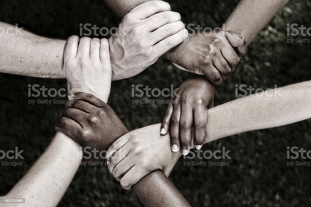 United we stand: six clasped hands in black and white stock photo