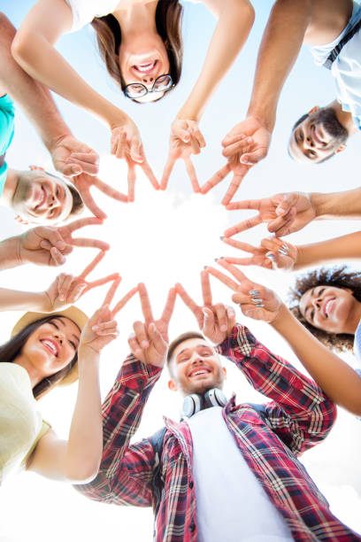 unity and connection of people. topview of multi ethnic students friends, putting their fingers together, wearing casual clothes, otdoors on a sunny day. conception of successful teambuilding - mano donna dita unite foto e immagini stock