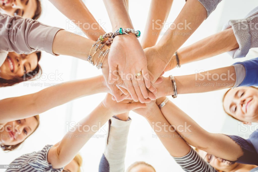 Unity and cooperation Low angle view of women making a pile of hands. Group of female with stack of hands. A Helping Hand Stock Photo
