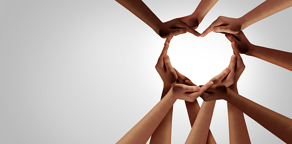 Unity and diversity partnership as heart hands in a group of diverse people connected together shaped as a support symbol expressing the feeling of teamwork and togetherness.