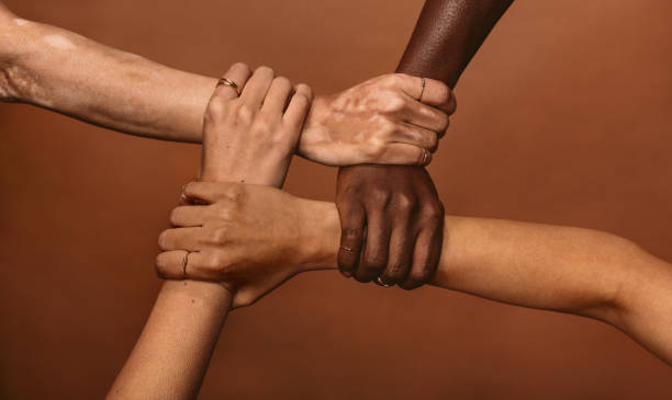 Unity in diversity Four diverse women holding each others wrists in a circle. Top view of female hands linked in the lock against brown background. four people stock pictures, royalty-free photos & images
