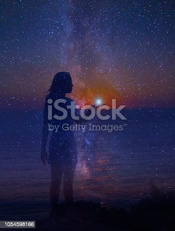 The night sky full of stars and a silhouette of a standing girl with a star in her hand.